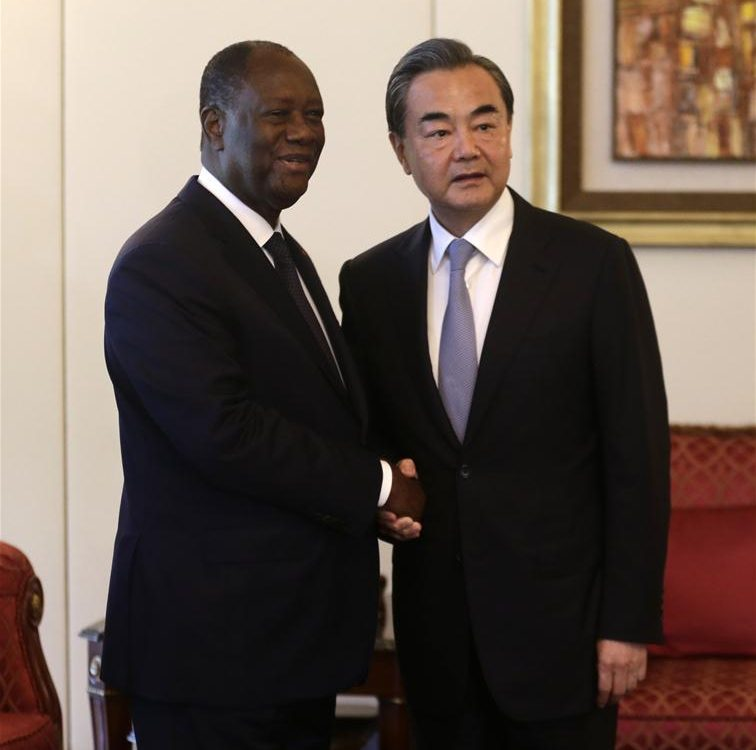 Cote d'Ivoire President Alassane Ouattara (L) shakes hands with Chinese Foreign Minister Wang Yi in Abidjan, Cote d'Ivoire